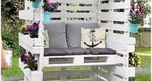 Geschlossener Sitzbereich mit Holzpaletten und bequemen Kissen