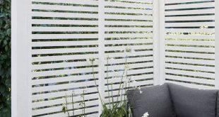 Sitzbereich im Innenhof mit vertikalem Sichtschutz aus Holzlatten und weißer ...