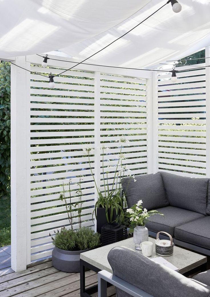 Sitzbereich im Innenhof mit vertikaler Privatsphäre aus Holzlatten und weißen ...