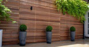 Baue einen Holzzaun und ein Sichtschutzschild im Garten